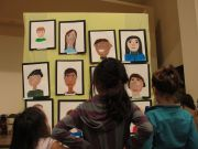 Students look at self portraits